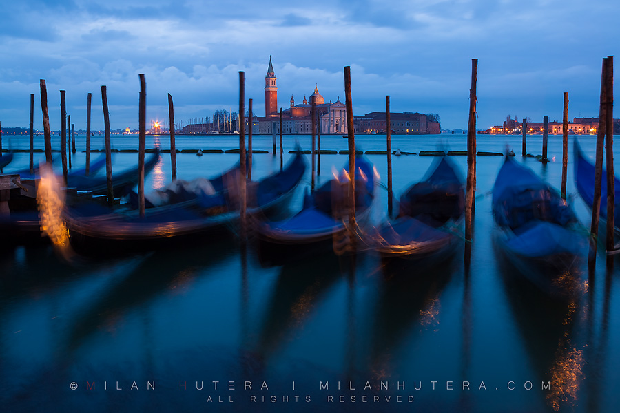 A dark and cloudy March morning in Venice. The sway of gondolas is exaggerated by long exposure. The iconic church of San Giorgio Maggiore can be seen in the backgroung.