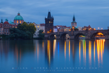 A peaceful evening without tourist boats on river Vltava, near Charles' Bridge. The town silouette from the left: Towers of Clementinum, The dome of Church of Saint Francis of Assisi, Old Town Bridge Tower and the Tower of Charles' Bathhouse