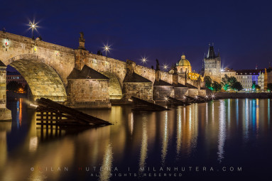 Quiet summer twilight at Charles' Bridge in Prague. The dome of the Church of Francis of Assisi and Old Town Bridge Tower are visible in the back.