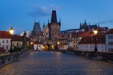 A warm summer dawn near Charles' Bridge Towers on Malá Strana. The Prague Castle with St. Vithus Cathedral is visible in the distance.