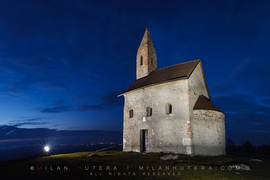 A cloudy winter evening at the Church of Saint Michael Archangel near Nitra, Slovakia. This tiny Romanesque church is one of the oldest churches in Slovakia. It is also one of the most famous ones. The church lies on a cliff above the village of Drazovce. The twinkling lights of nearby villages and a busy road can be seen in the distance.