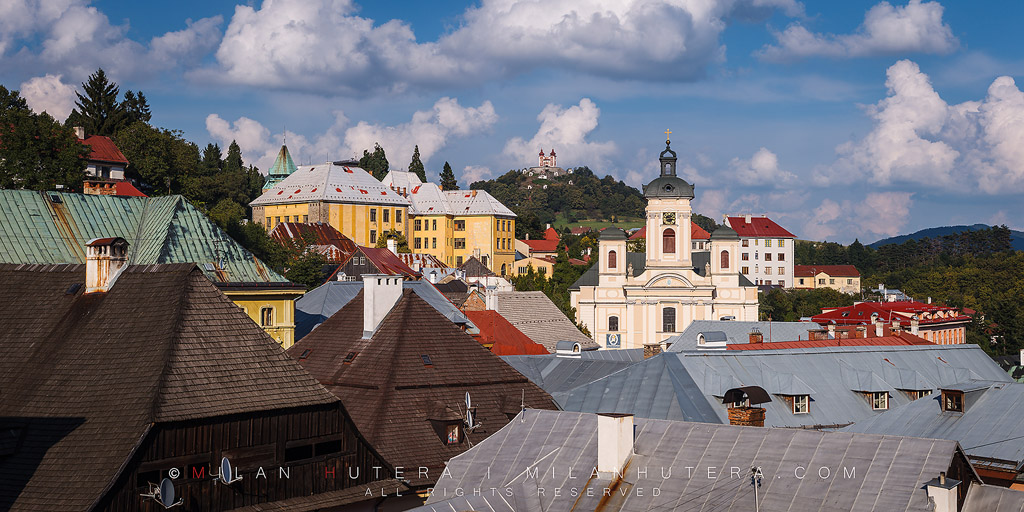The old mining town of Banska Stiavnica is one of the most important landmarks of Slovakia and it is a part of UNESCO World Heritage Site since 1993. The mines around town were rich in silver ore and other precious metals. The town was also a home to first mining college in Europe and the first ever Technical School in the world - established in 1763. This photo depicts a late August afternoon overlooking the rooftops of the historic center of Banska Stiavnica. The metal and wooden rooftops are a necessity due to large snowfall in winter months. The hilltop Calvary, which is perhaps the town's most famous landmark, is visible in the distance.